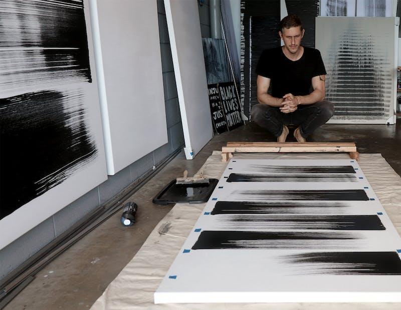 Kamran Samimi working on a painting in his studio.
