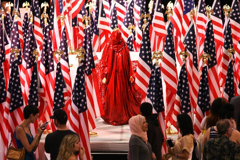 Woman in sequined red chador standing in the center several American flags.