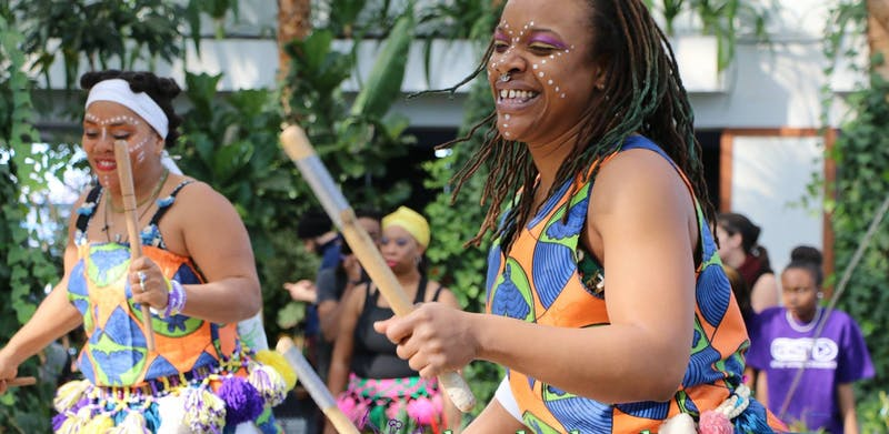 Ayodele Drum and Dance group performing and having fun during a daytime performance.