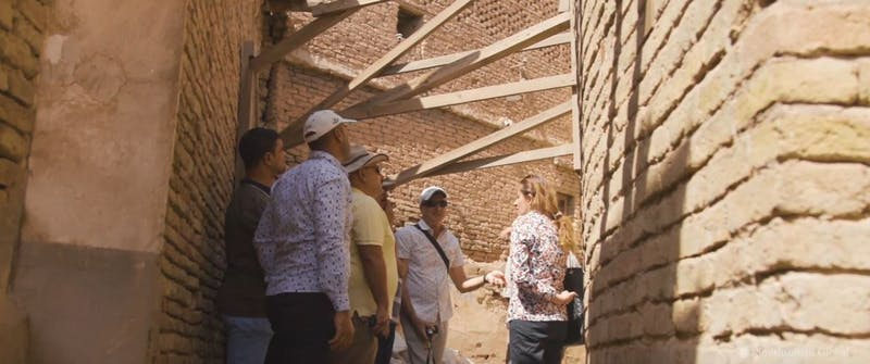 Conservator, Kent Severson, stands in a group of people in discussion as part of the Nimrud Rescue Project.