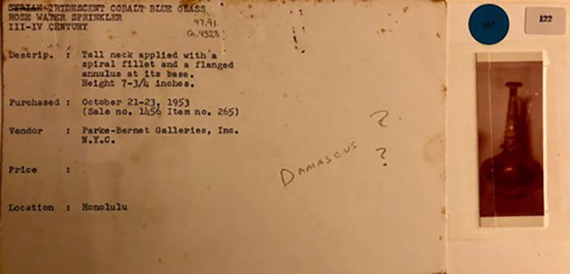 """Figure 2: Shangri La archival object notecard with text from Kelekian's 1953 auction sale catalogue, attributing the sprinkler to Syria. An early guess of its provenience is seen in the handwritten note reading """"Damascus?"""", which recent research has revealed to be inaccurate."""