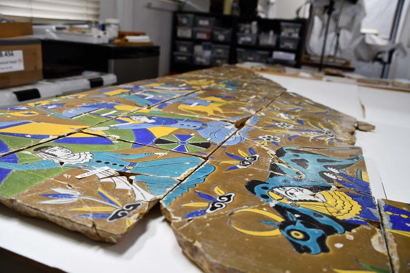 Photo of ceramic tiles in conservation lab. Two figures on tiles. Male figure crouching on the left wearing a real rob. Other parts of the scene are not easily visible.