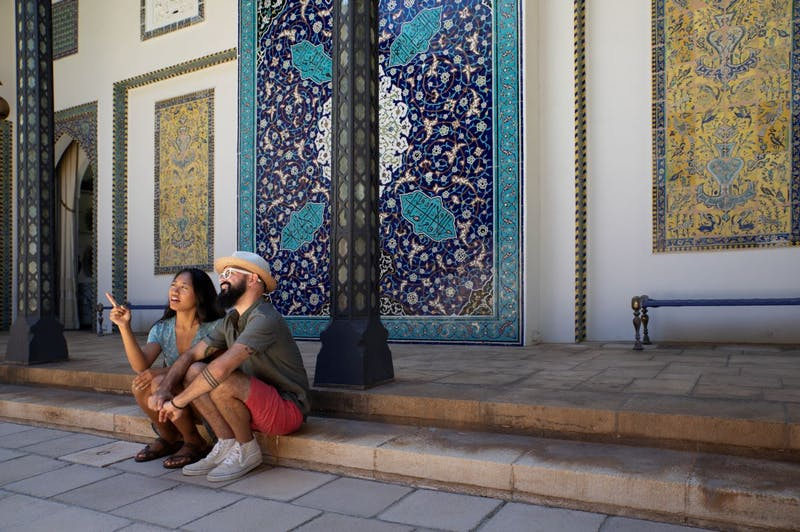 A woman and man sitting on the steps of the courtyard looking and pointing at the opposite side of the room.