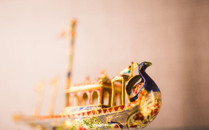 Close-up view of a Mughal miniature artwork. The three-dimensional peacock boat with colored enamel surface.