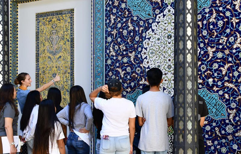 Photograph of Shangri La guide and students discuss the mosaic in the museum's central courtyard.