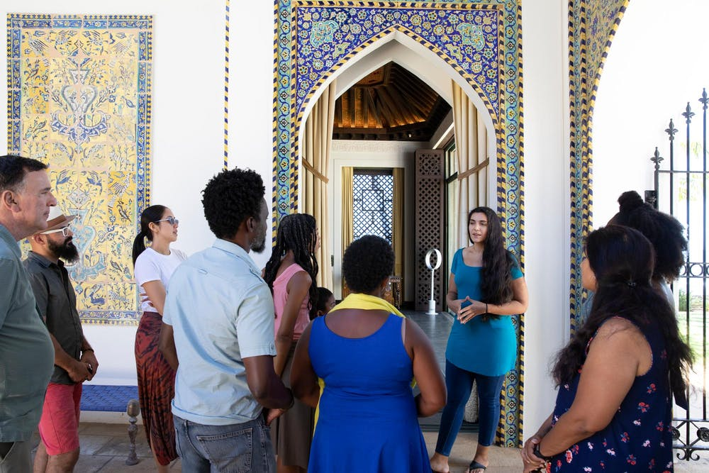 Group of nine visitors gathered around a tour guide in the Central Courtyard of Shangri La.