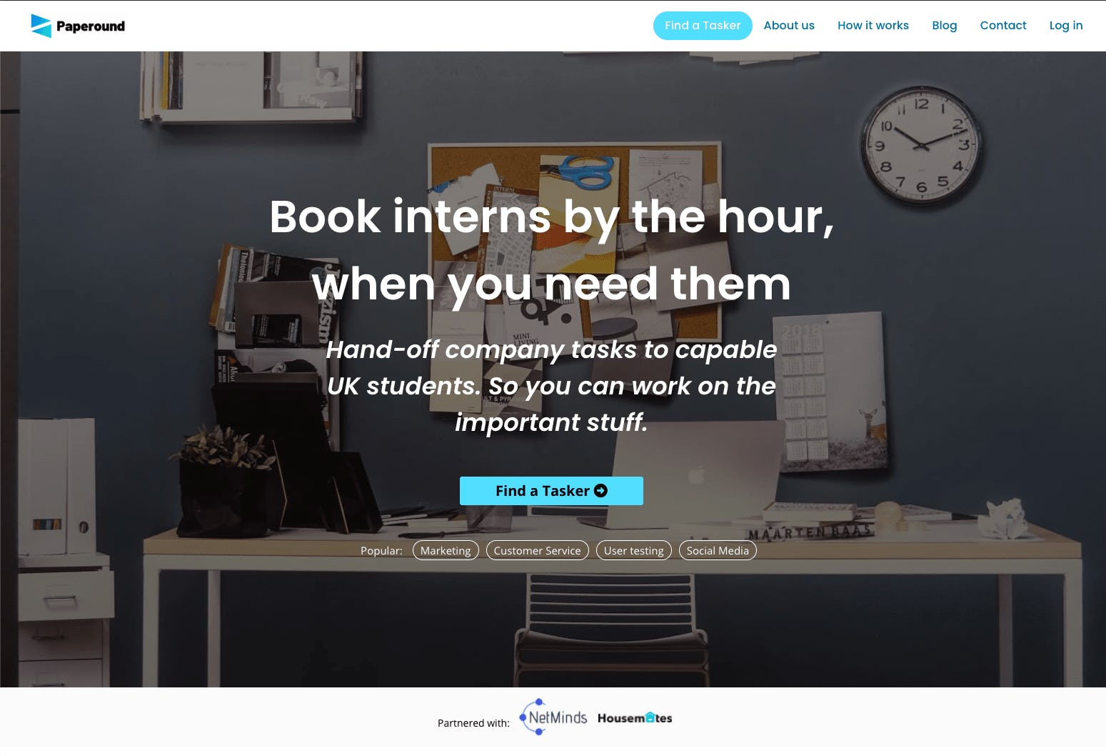 Screenshot of the service marketplace Paperound's landing page header featuring an office desk.