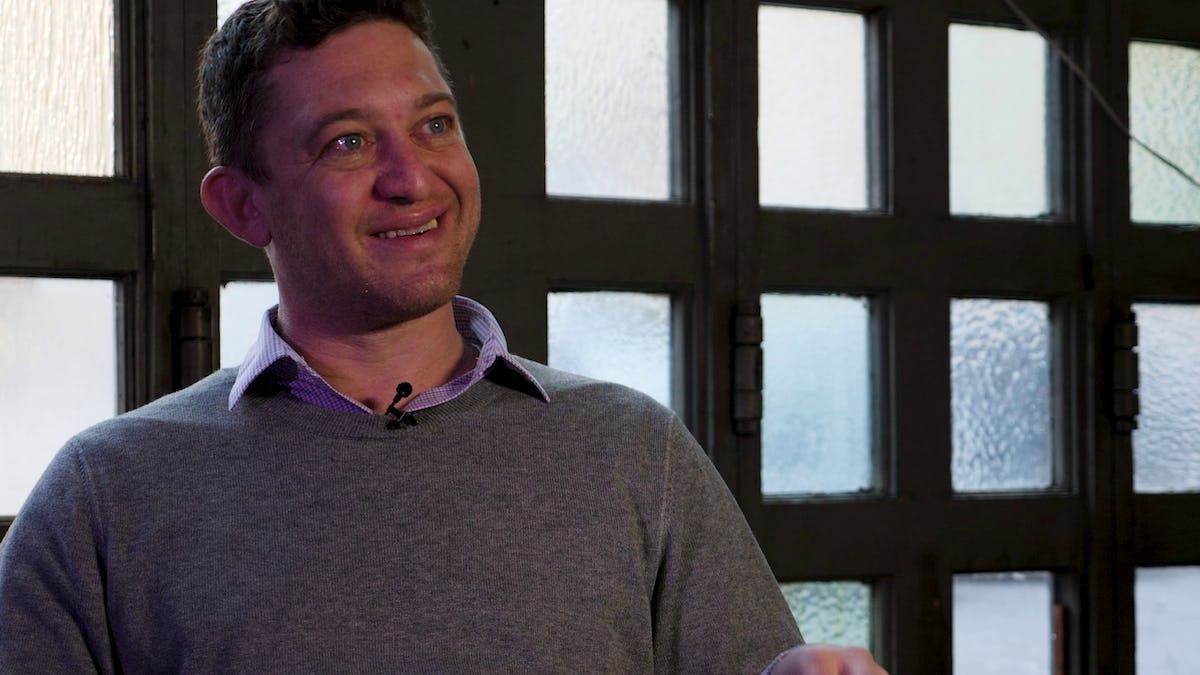 Investor Josh Breinlinger in a 1/3 close up wearing a grey sweater smiling