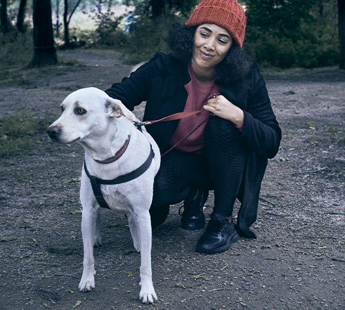 A woman crouching with her dog on a lead