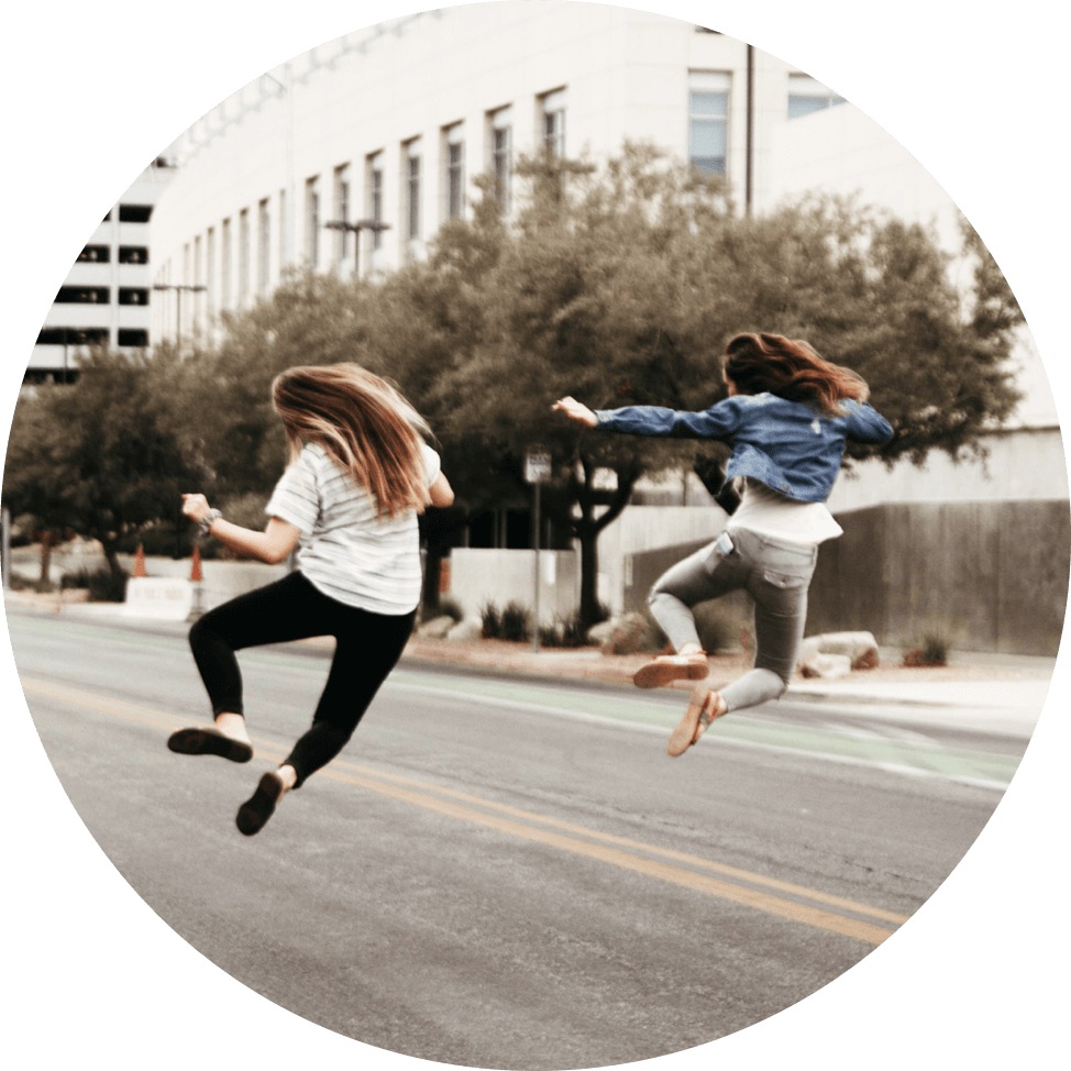 two women jumping in the street synchronously
