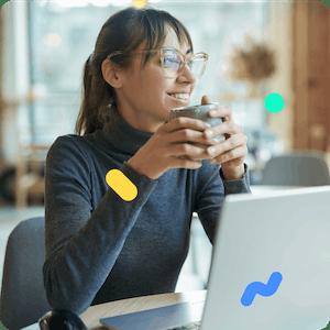 Photo d'une femme tenant une tasse devant un ordinateur