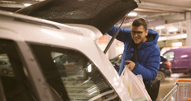 Imagem de homem a colocar saco na mala do carro