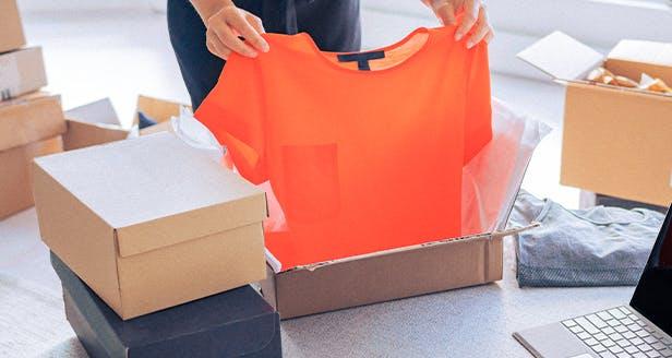 Imagem de uma pessoa a retirar uma blusa de uma caixa