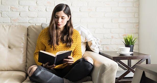 Fotografia de uma senhora a ler no sofá