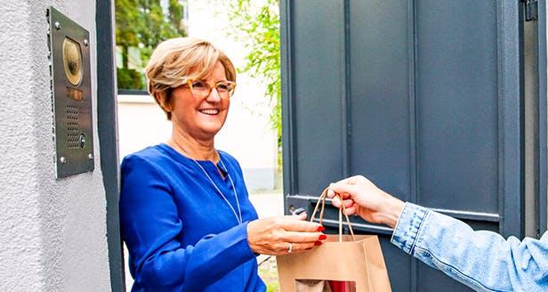 Mulher que recebe um saco de compras