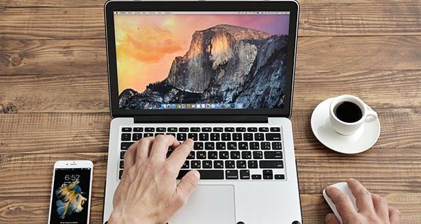 Fotografia de um computador, um telemóvel e um café