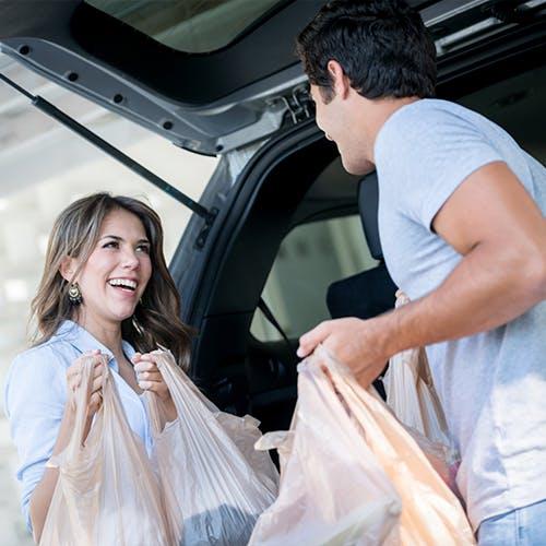 Fotografia de mulher e homem com sacos de compra ao pé de um carro