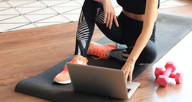 Imagem de uma senhora sentada num colchão ao computador