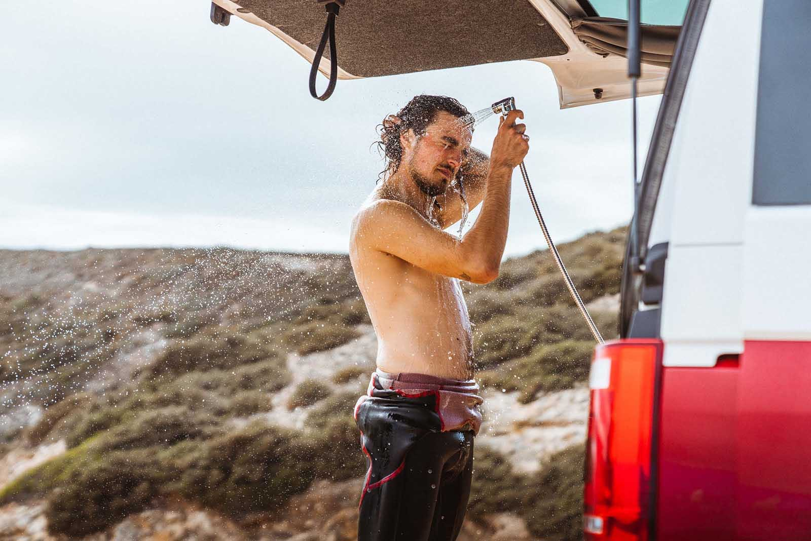 Surfeur utilisant une douche extérieure à l'arrière d'un van de surfeur Siesta Beach au Portugal.