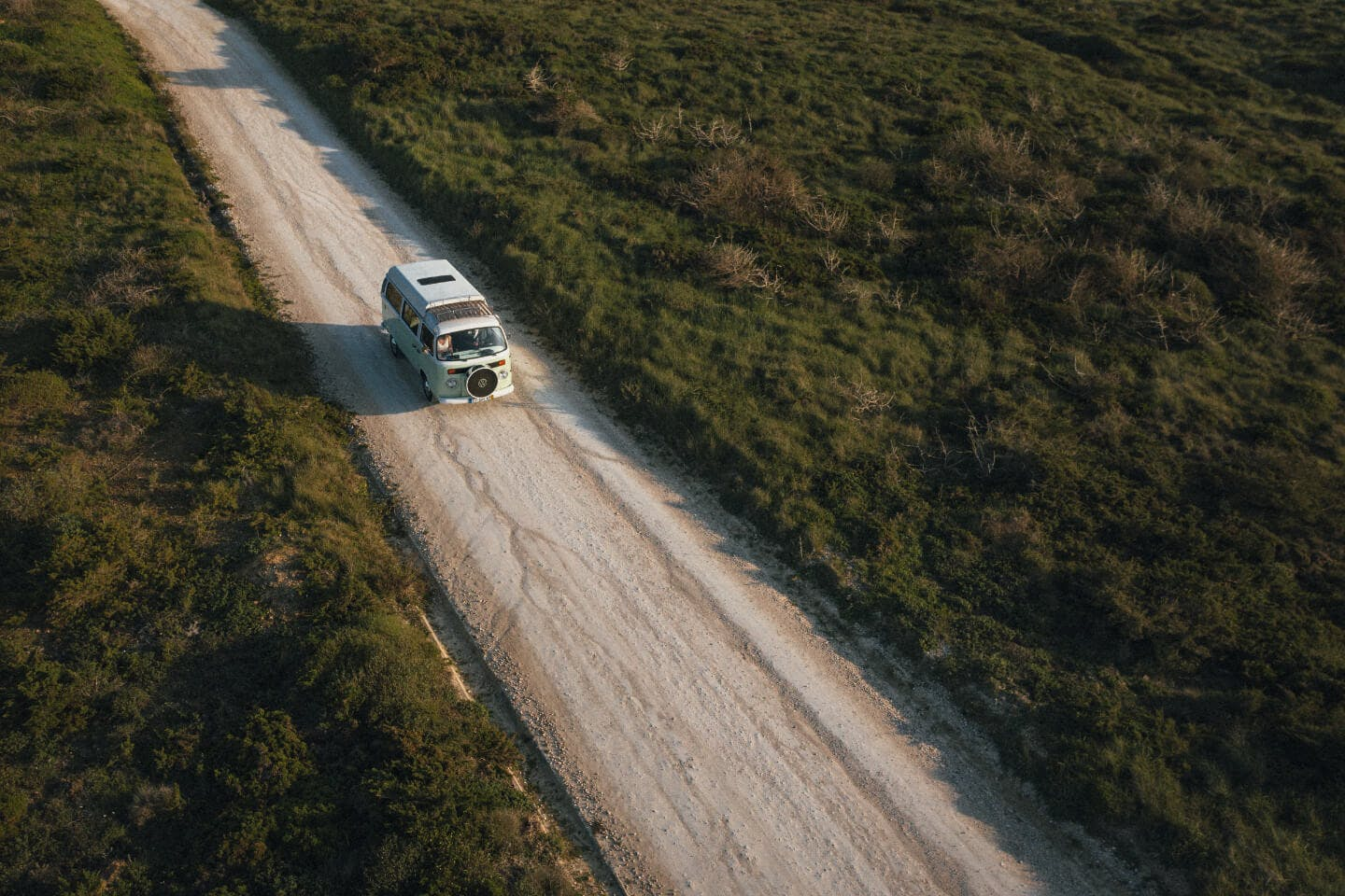 Vintage campervan driving along a dirt road from aerial perspective.