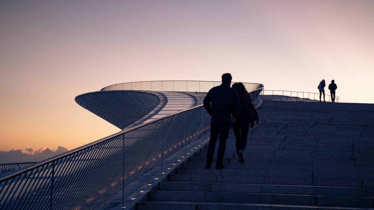 Couple watching one of the best sunsets in Lisbon at the MAAT museum.
