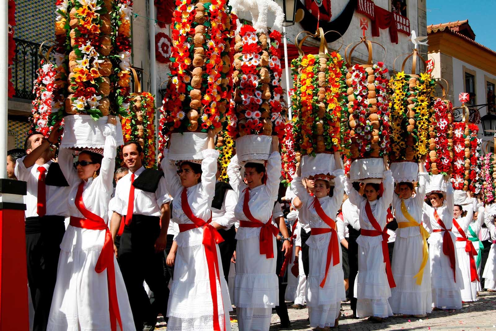 Elegant women parading with flower trays on their heads at the Festival of the Trays in Tomar, Portugal.