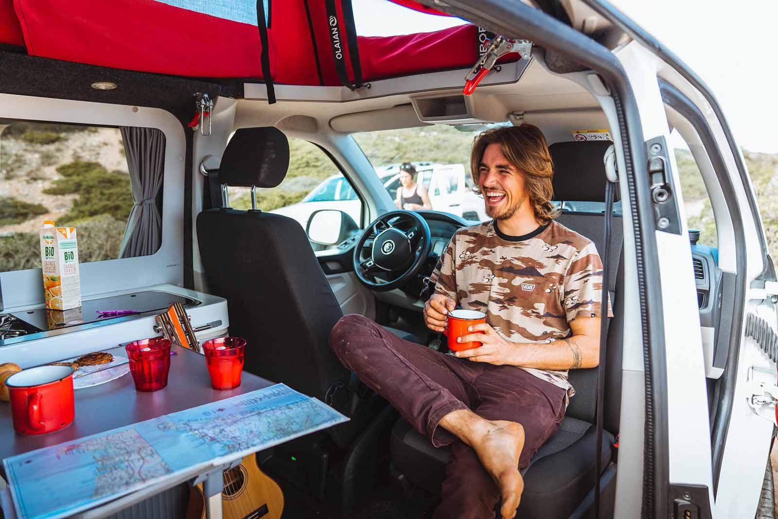 Surfeur qui se détend dans le van aménagé Siesta Beach aprés une journée à apprendre à surfer au Portugal.