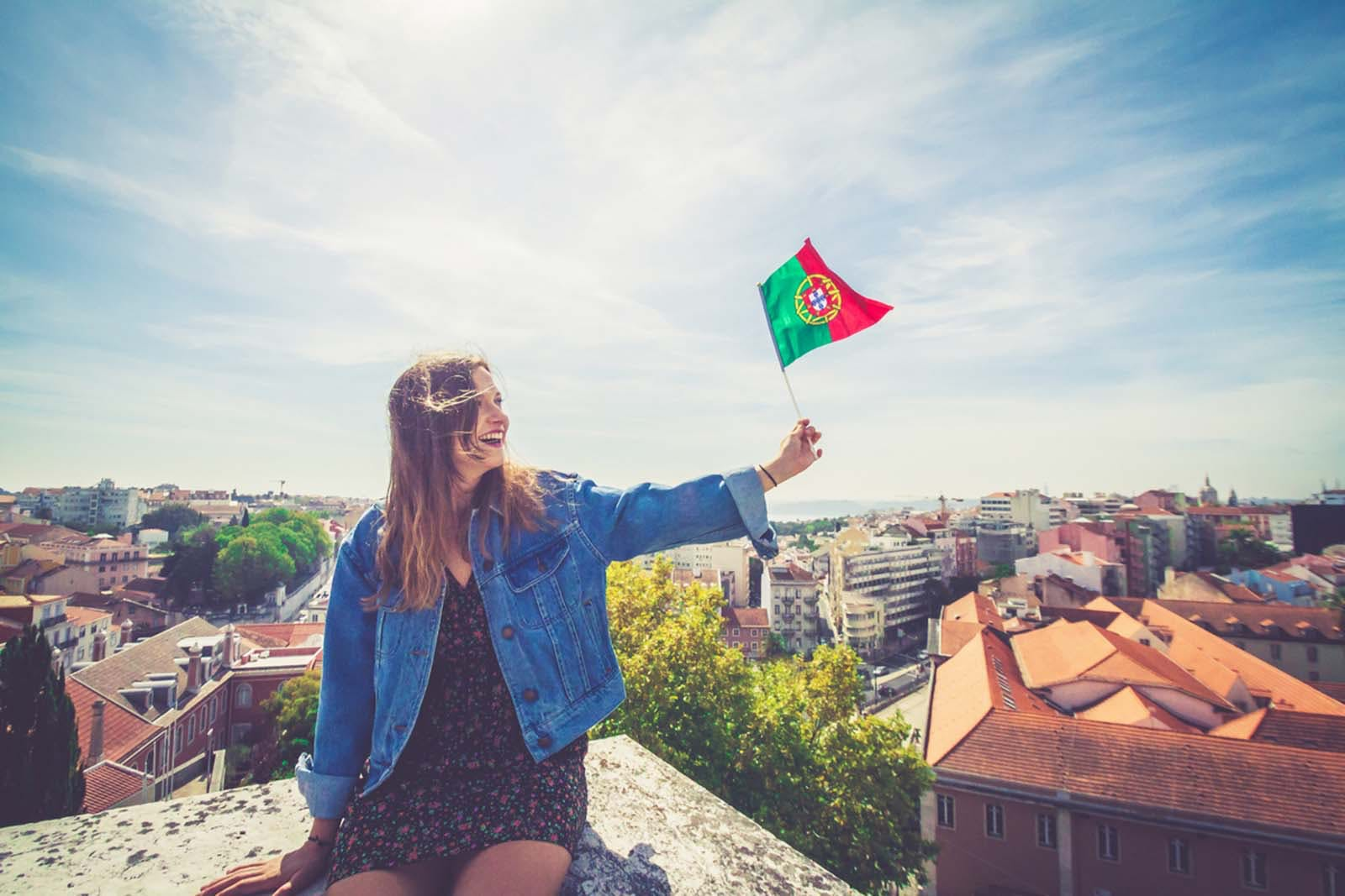 Woman holding up a small Portuguese flag during Portugal Day celebrations.