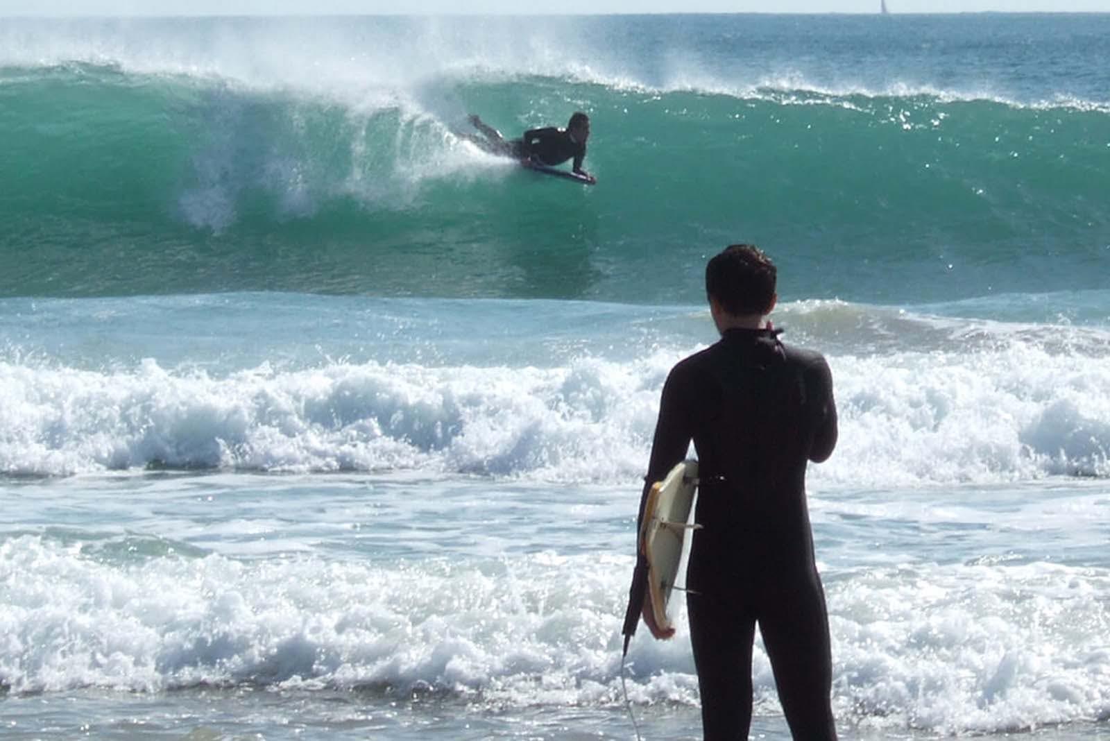 Surfeur regardant les vagues de Figueira da Foz depuis le rivage.