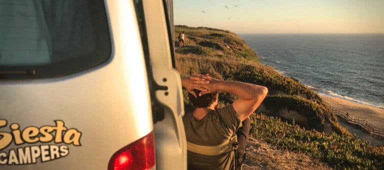 Camper enjoying a sunset view over a rugged cliff on the Portuguese coast.