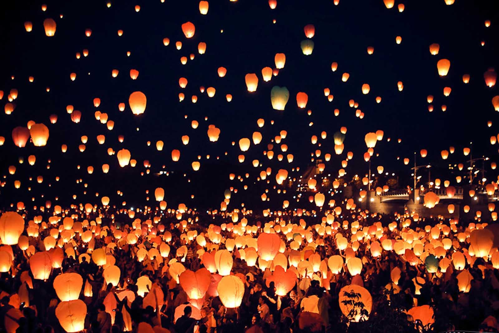 People lighting lanterns at night during Festival of São João.