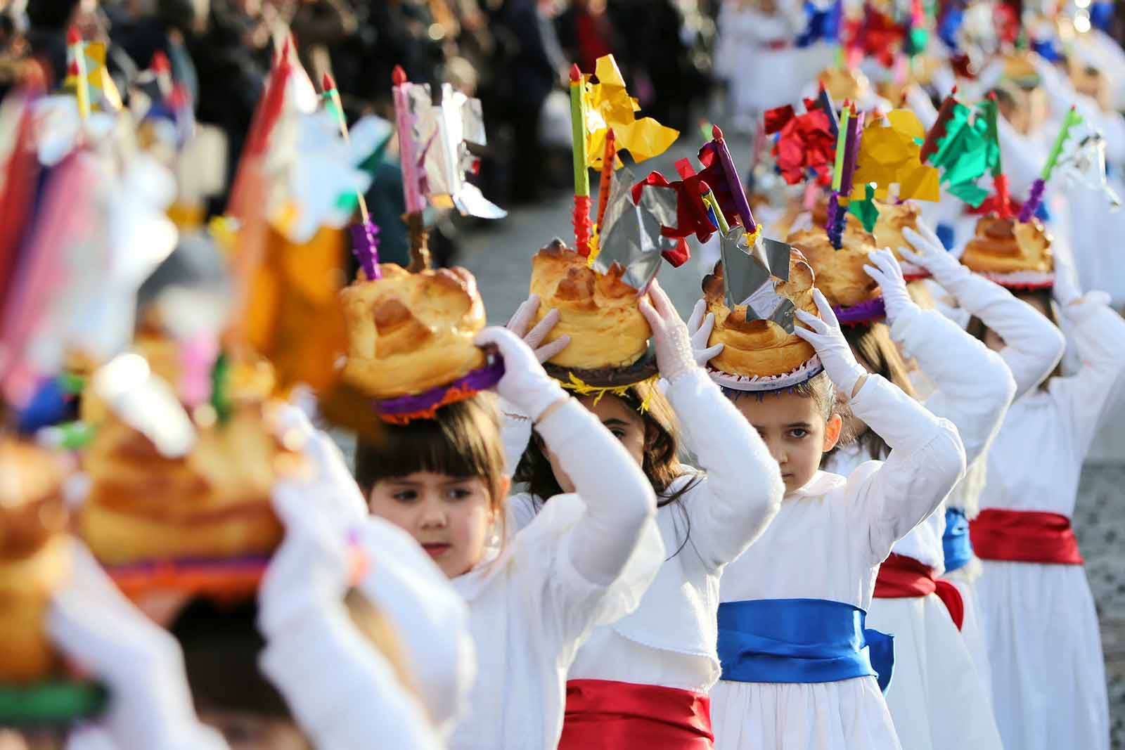 Young girls parading with fogaça cakes on their heads.
