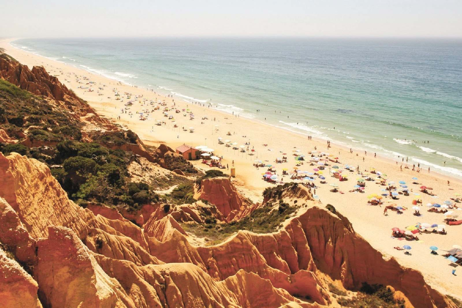 Praia da Gale with a view of the orange cliffs and the Atlantic coast near a campground.