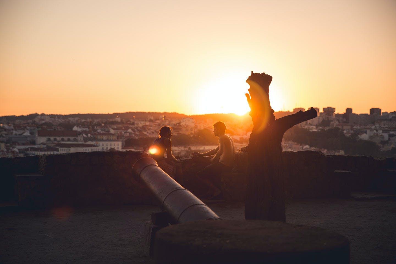 Couple regardant le soleil se coucher à l'horizon à Lisbonne, Portugal.