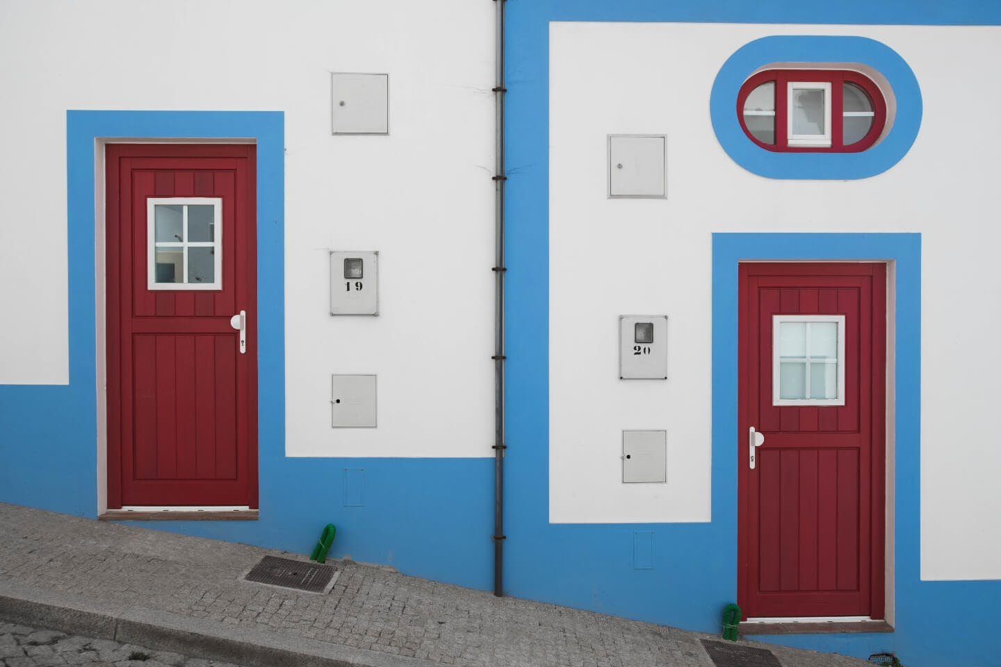 Charming white houses with blue trim and red doors in the Algarve.