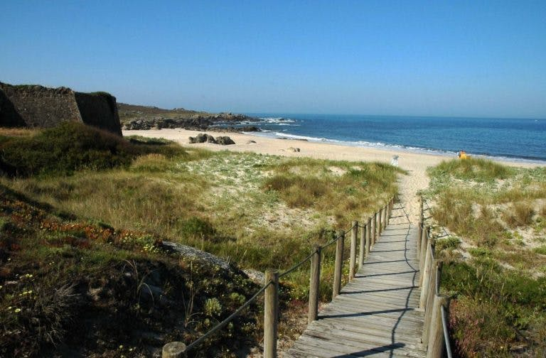 Wooden walkway leading to a sandy beach in Portugal.