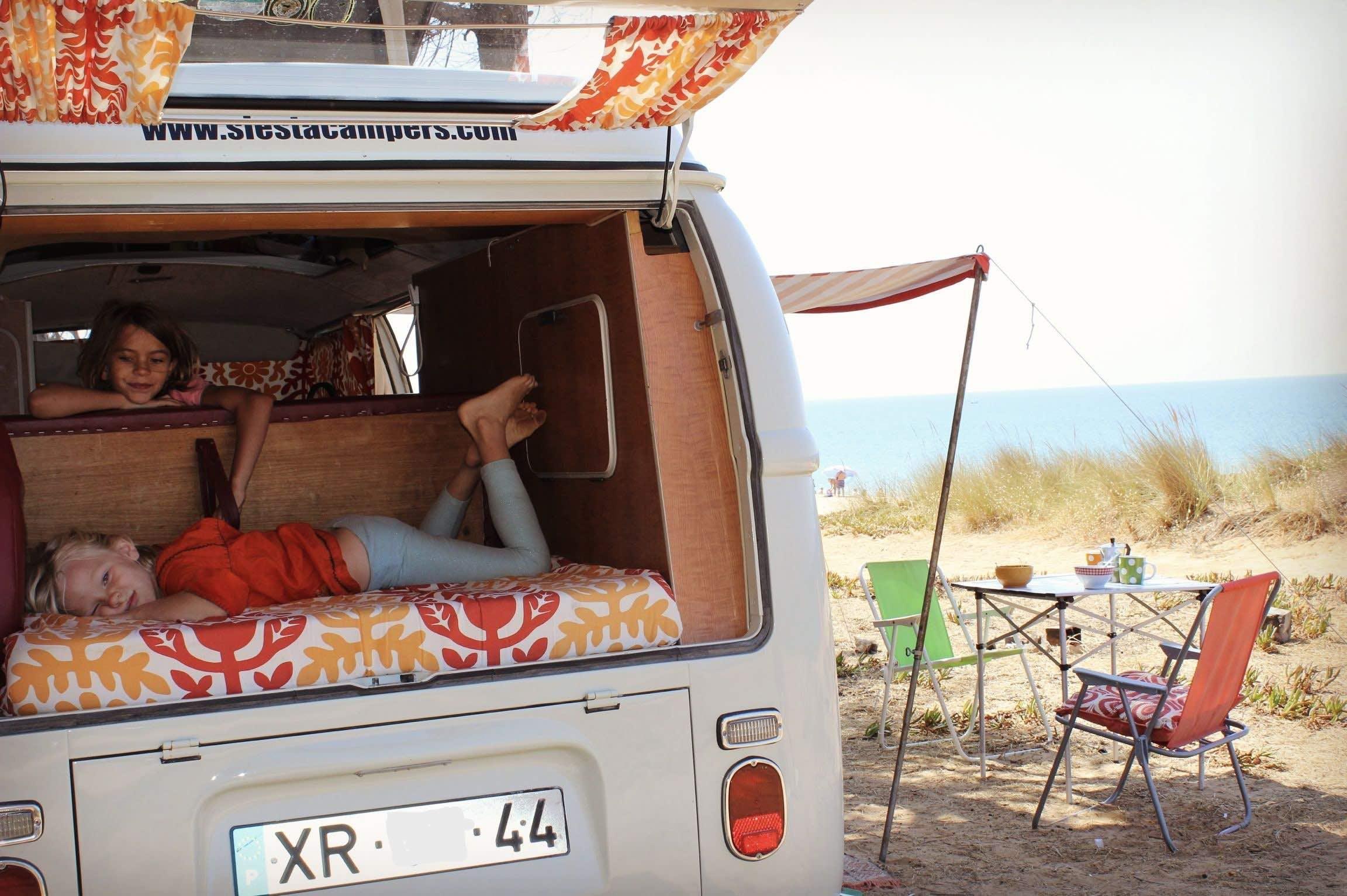 Kids enjoying the slow life in an old school campervan.