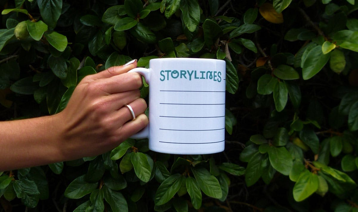 woman's hand holding out Storylines coffee mug in front of a green bush