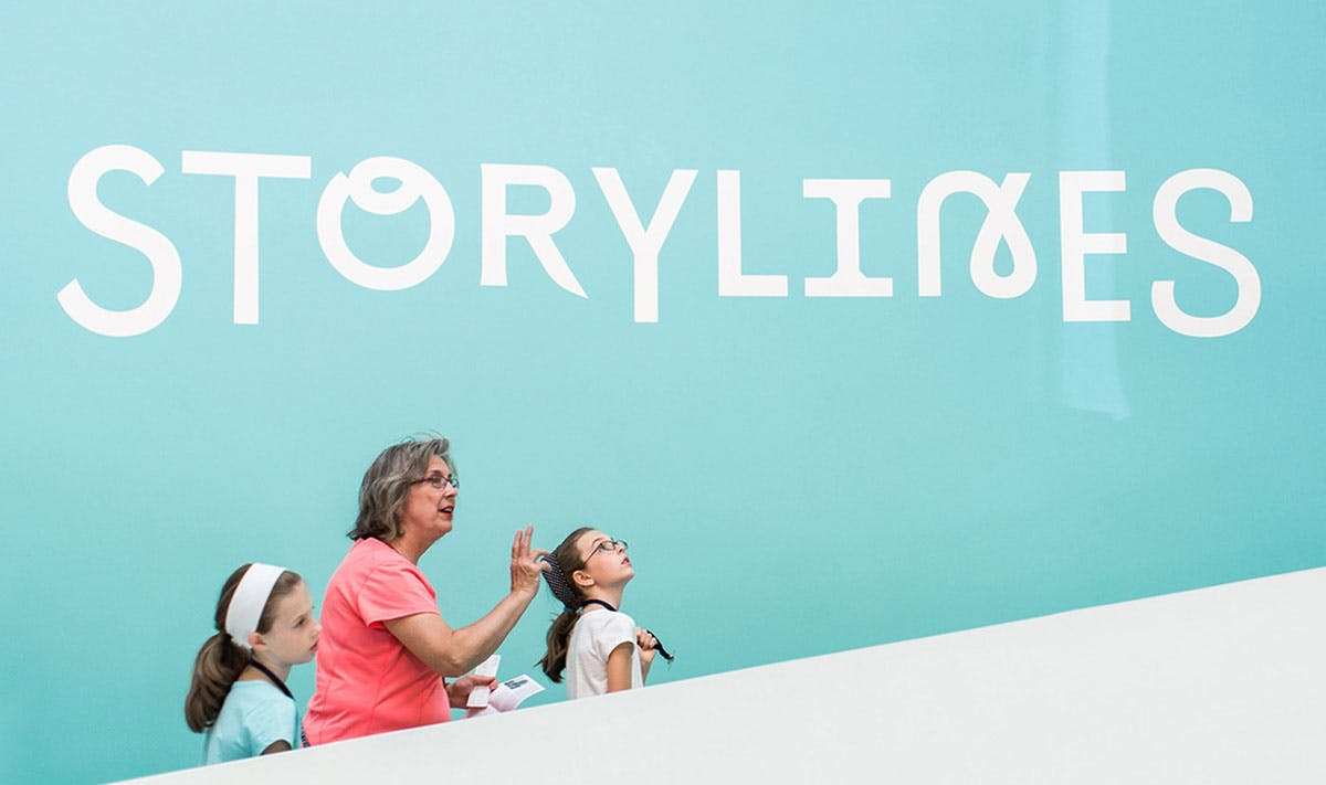 "Woman leading two young girls up stairs next to blue wall that reads ""Storylines"""