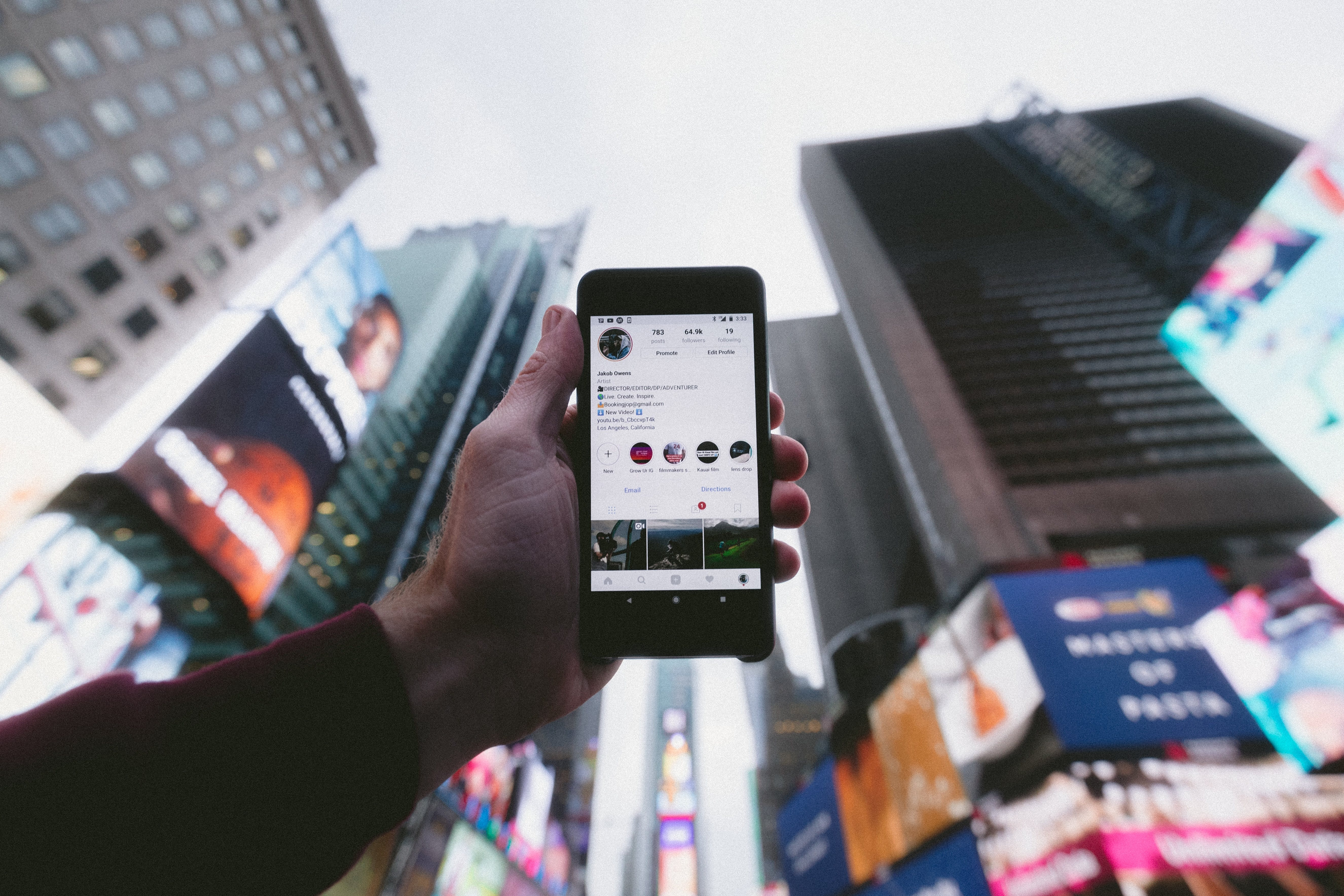 A person holding a phone that shows a instagram account onto the sky in a big city