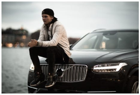 Tim 'Avicii' Bergling sitting on a Volvo with Stockholm in the background