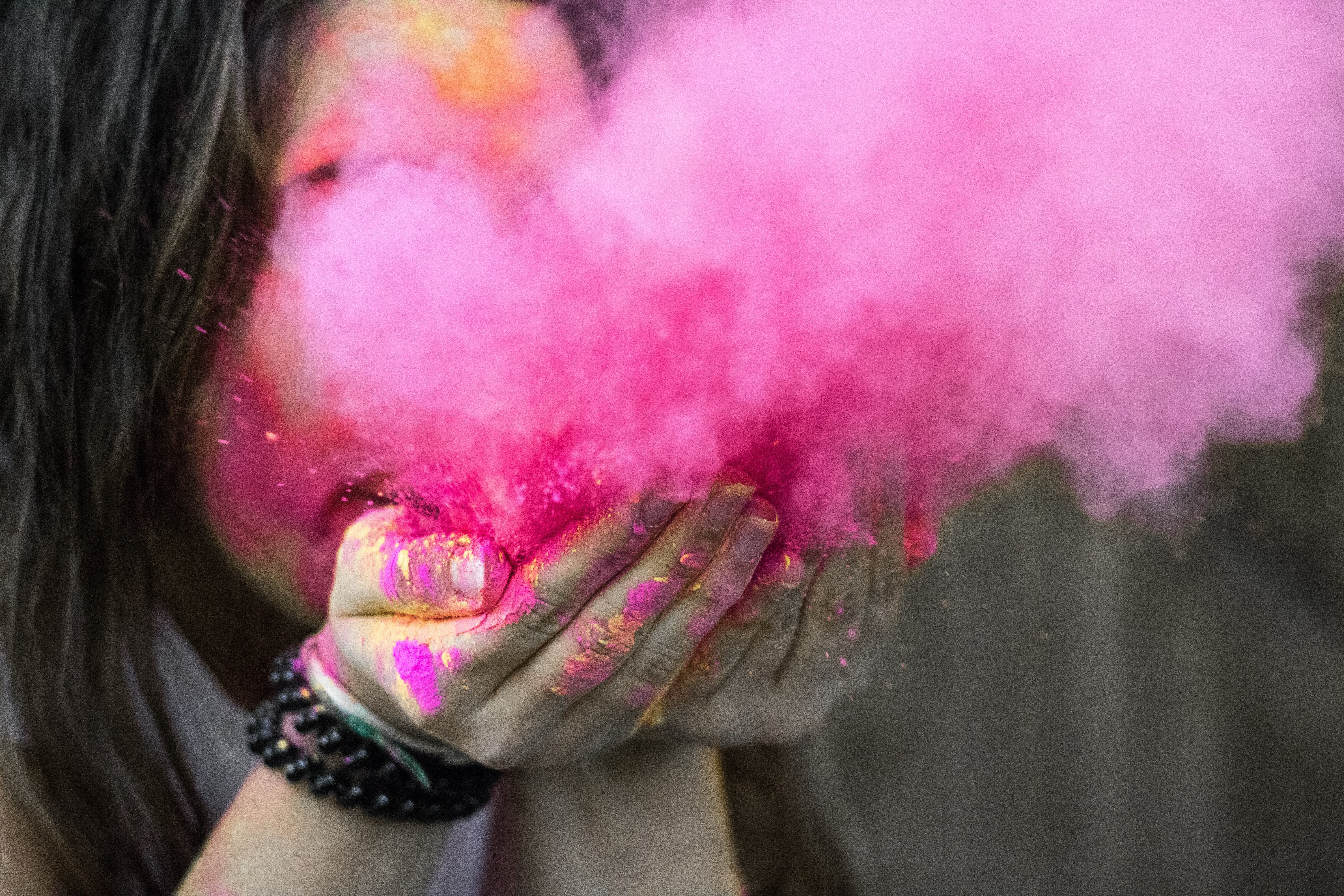 A girl blowing out pink powder so that it creates a pink smoke cloud