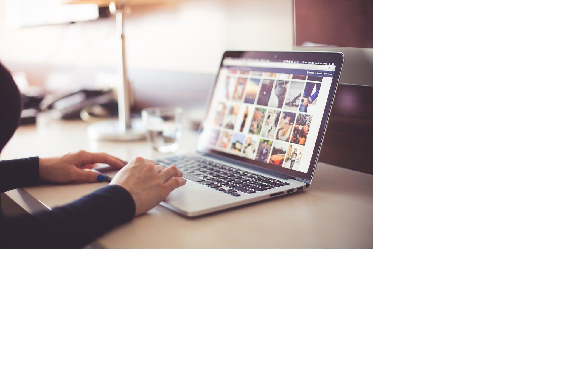 Kvinna sitter och kollar bilder på en dator i ett kontor