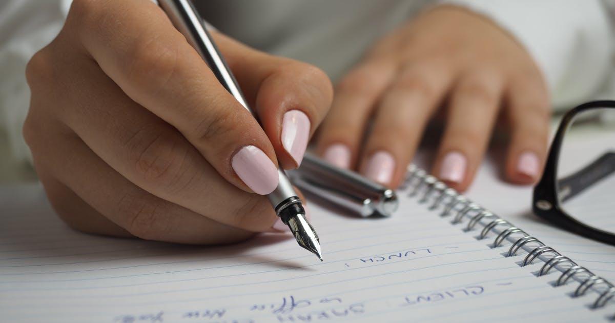 Tjej med Rosa nagellack gör anteckningar på ett block