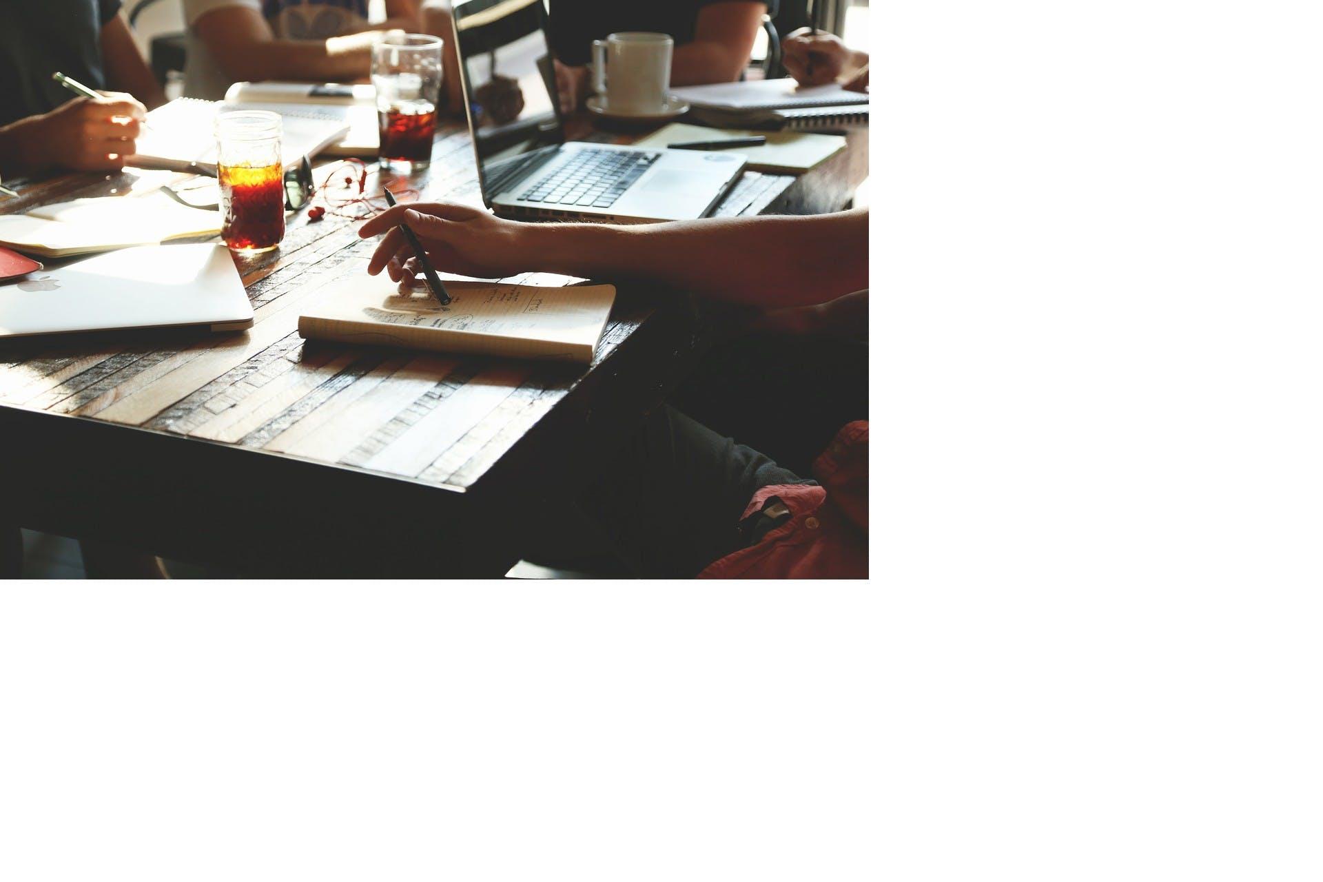 Några personer som sitter vid ett bord och planerar marknadsbudgeten