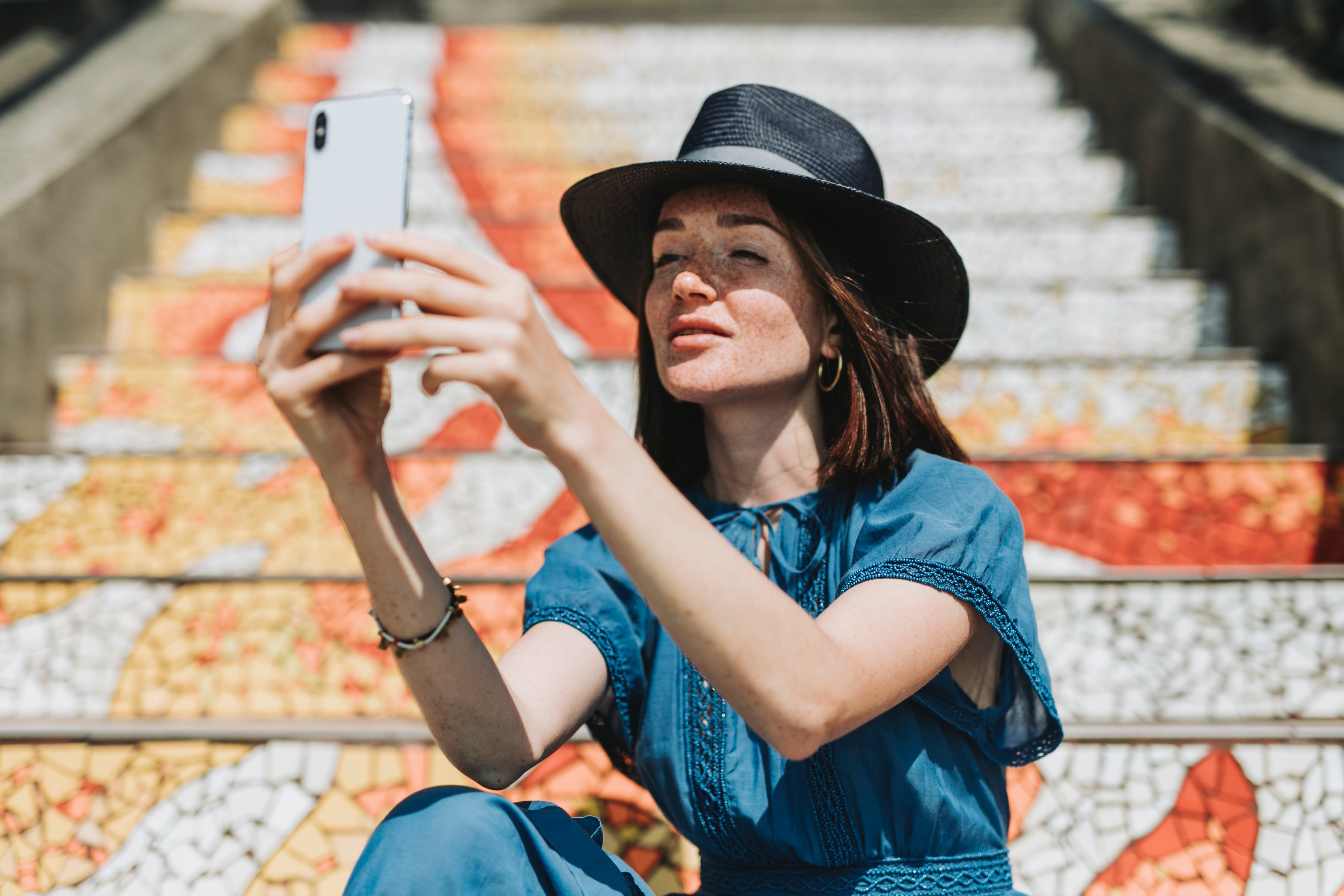 A girl sitting on a staircase and taking a selfie