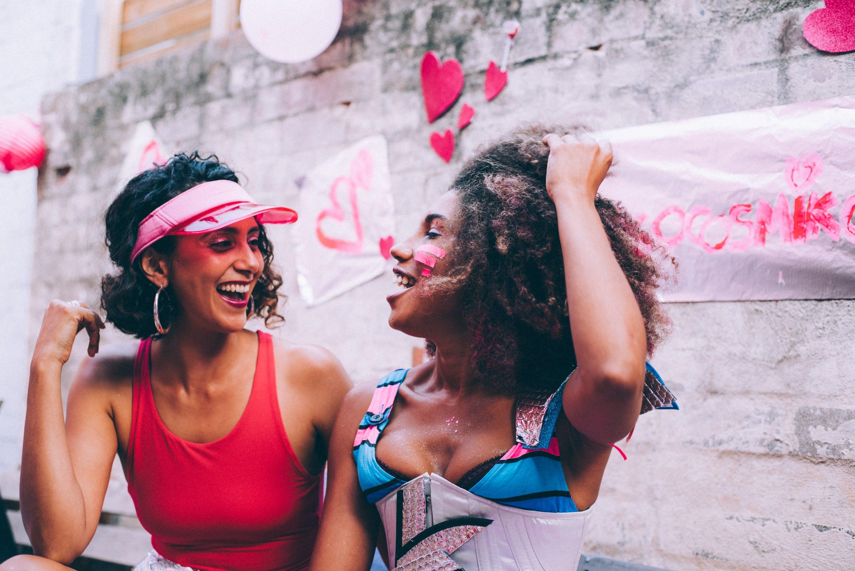 Två tjejer som skrattar tillsammans och poserar tillsammans med vägg som har hjärtan på sig