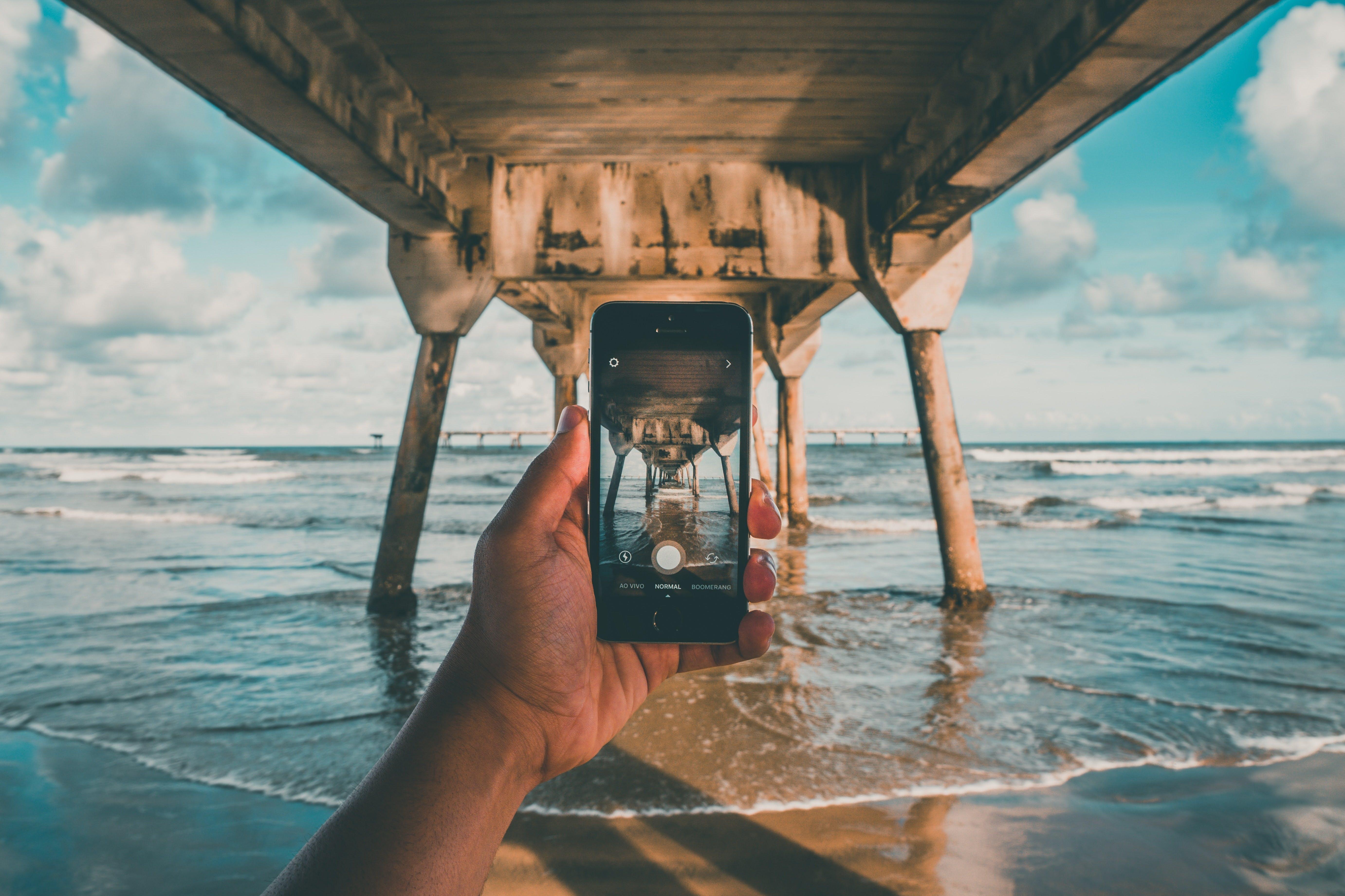 En person som håller i en mobil som har kameran öppen som tar ett foto under en brygga på en strand