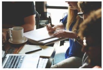 Grupp med människor som sitter vid ett bord och gör anteckningar och jobbar på sin macbook