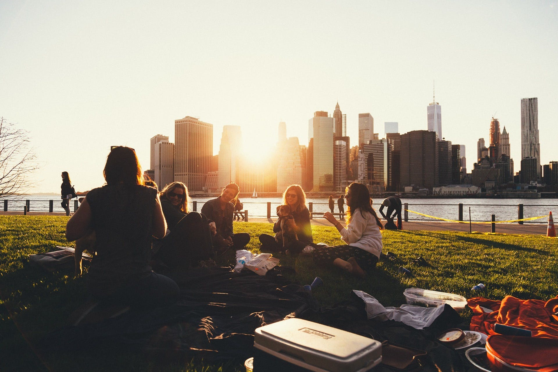 A group of people sitting down in the park at sunset in New York